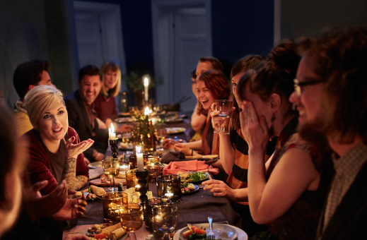 A well-laid dining table with lit candles and many happy guests.