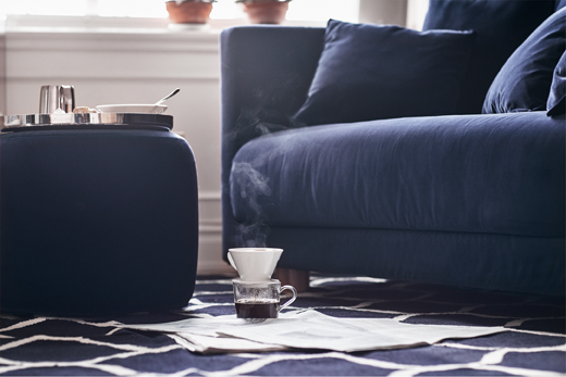 Close-up of a two-seat sofa with a dark blue velvet cover and lots of cushions, shown together with a pouffe in the same cover.