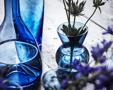 Close-up of handmade vases and carafes in different shapes and sizes, all made of blue glass.
