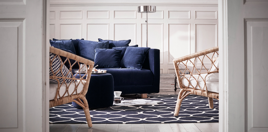 A two-seat sofa with a dark blue velvet cover and lots of cushions, shown together with a pouffe in the same cover and two rattan armchairs.