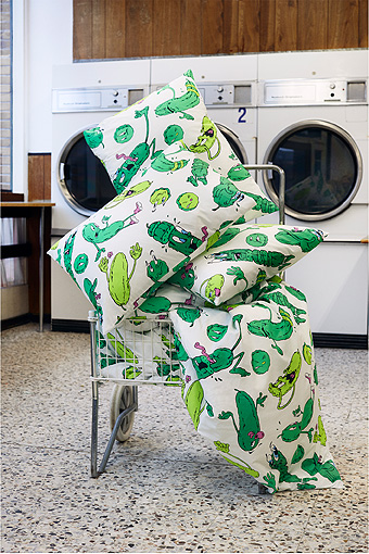 A laundry cart filled with quilt covers and pillowcases with fun cucumber pattern.
