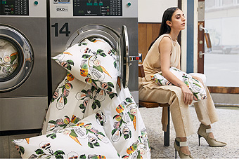 A woman sitting beside a washing machine and colourful quilt covers and pillowcases falling out of the machine.