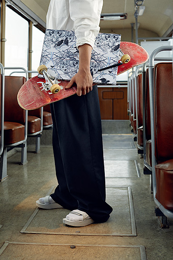 A man standing in the gangway of an empty bus, with a skateboard and a sketch book under his arm.