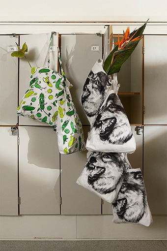 Textile bags with cucumber and wolf patterns hanging on locker-doors.