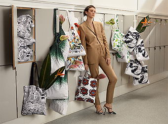 A woman standing in a corridor leaning against some cabinets, around her hangs textile bags with various patterns.