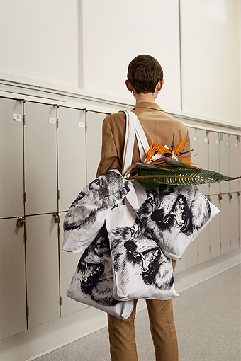 A woman standing in a corridor with several textile bags on her shoulder.