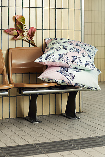 A bench with two cushions featuring a pattern with doves.