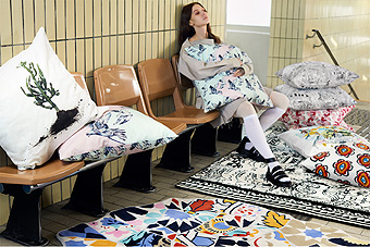 A woman sitting on a bench surrounded by cushions in various patterns and on the floor lies two rugs.