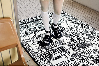 A woman standing on a rug with a funny black and white pattern.