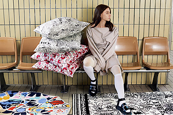 A woman sitting on a bench with a pile of cushions in various patterns beside her and on the floor lies two rugs.