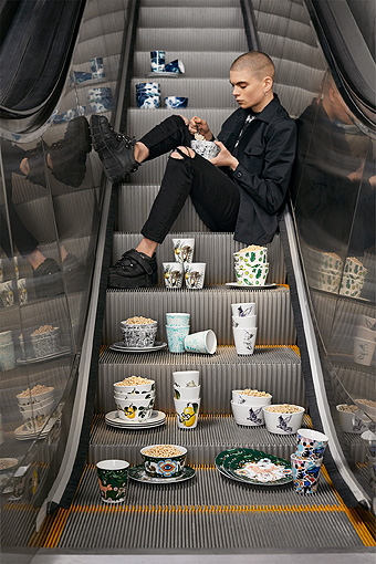 A man sitting in an escalator holding a bowl and in front of him a display of mugs, bowls and plates in various patterns.