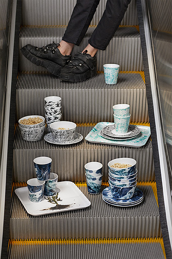 Mugs, bowls and a tray with various patterns displayed in an escalator.