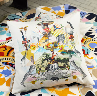 A pile of cushions featuring a colourful pattern shown on a colourful rug.