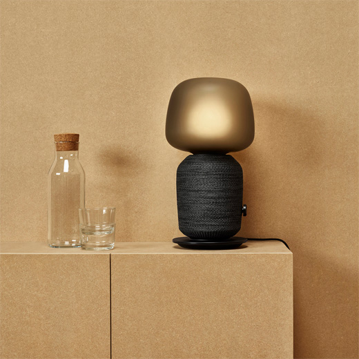 A black SYMFONISK table lamp with built-in WiFi speaker, on a bench next to a glass of water, in a minimalistic room.
