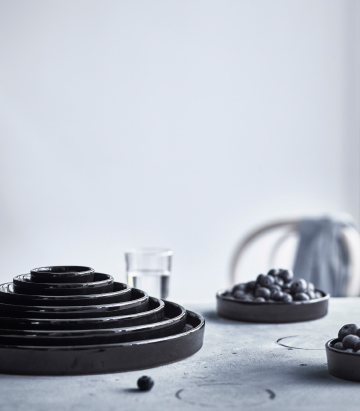 Black serving plates stacked in the shape of a pyramid.