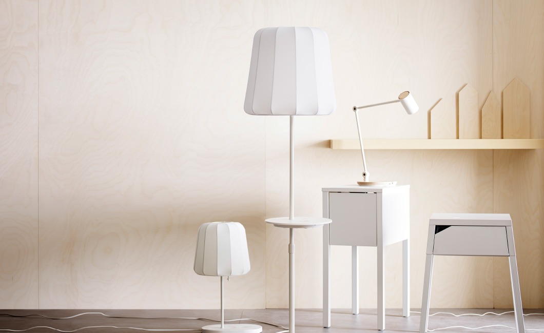 A display of lamps and bedside tables with wireless charging.