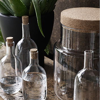 Close-up of handmade glass bottles and jars, completed with cork lids.