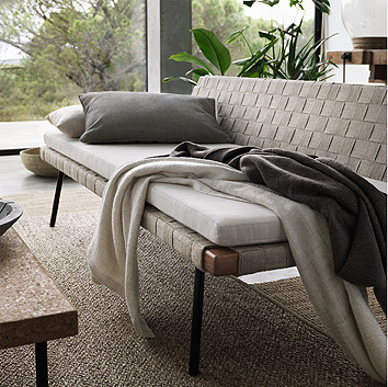 A beige day-bed with woven seat and back shown with a thick mattress pad, grey and beige cushions and blankets.
