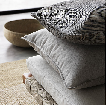 A pile of cushions in a beige cotton/linen blend.