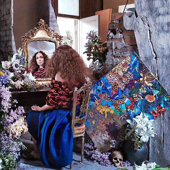 A woman sitting in front of a mirror with gold ornaments, she is dressed in a cornflower blue skirt and a red/black top, beside her is a large poster of colourful butterfly wings.