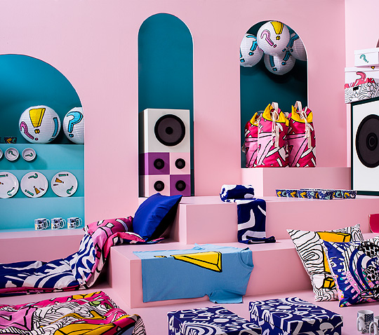 A display of a colourful collection with fun patterns consisting of tableware, boxes, textiles and pendant lamps.