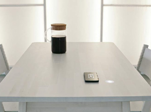 dining table with a glass jug filled with coffee and a smart phone next to a built-in charger in the table top.