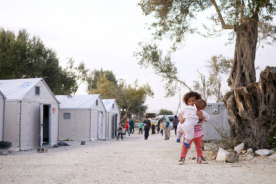 A girl holding her baby sister, with shelters in the background.
