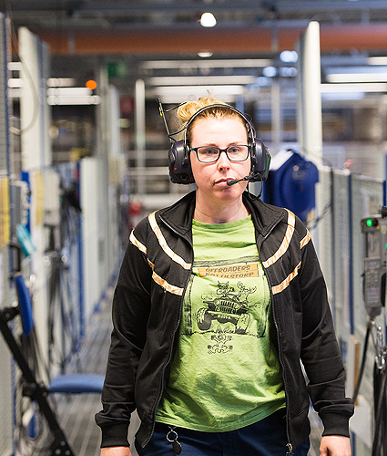 A woman with headset walking through the factory.
