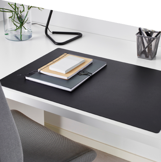 A black rectangular desk pad on top of a white desk and some note books.