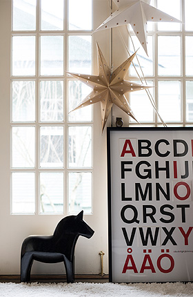A black Swedish Dala horse, a gold-coloured Christmas star and a black picture frame with a poster with capital letters shown in front of two French doors.