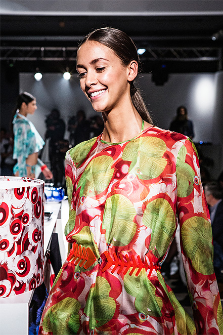 model in a colourful dress on the runway at the Milan fashion week.  And in the background you can see a white lamp shade with red eyeball pattern.