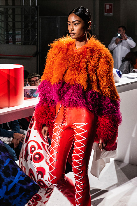 A model in an orange fur jacket together with red leather trousers decorated with white strings, on the runway at the Milan fashion week. And in the background you can see a white fabric with red eyeball pattern.