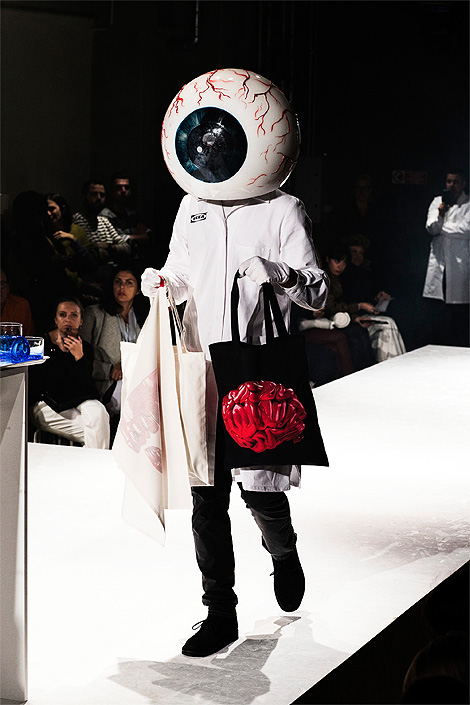 A model in a white coat carrying a black bag with a red brain pattern and a big eyeball helmet, on the runway at the Milan fashion week.