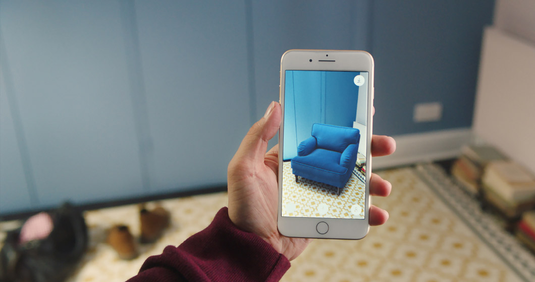 A smartphone showing IKEA STOCKSUND armchair virtually placed in an empty corner.