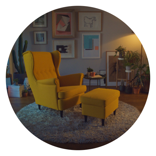 IKEA STRANDMON armchair and footstool in yellow shown in a cosy living room setting.
