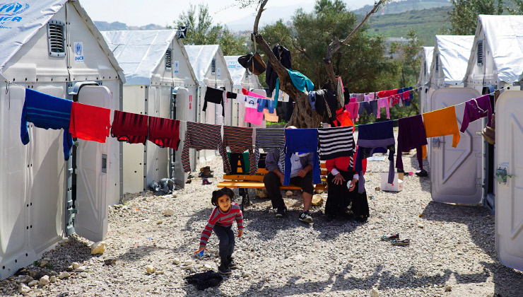 A refugee child playing amongst washing hanging to dry between two rows of Better Shelters.