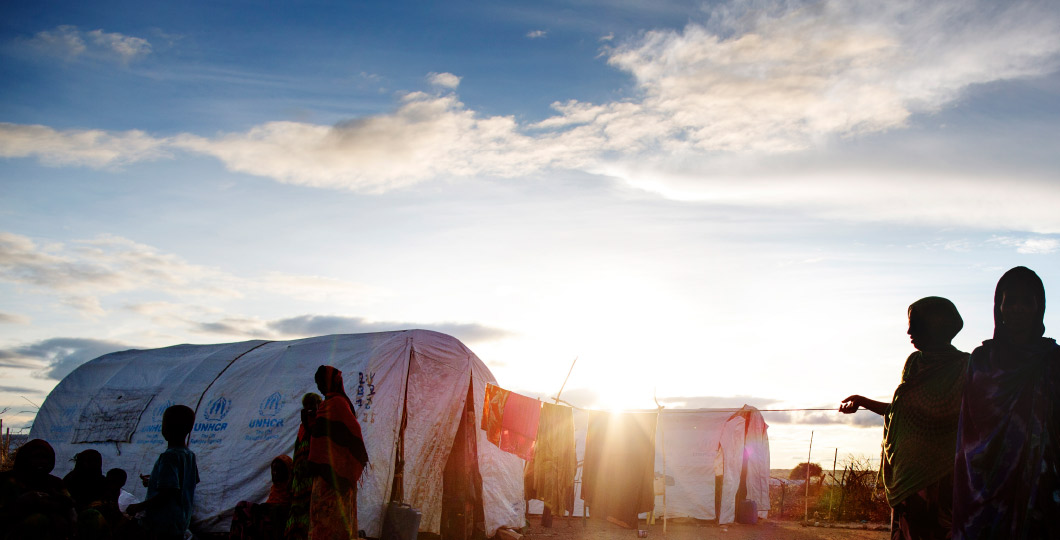 Sunrise in a refugee camp, the tents and a few refugees silhouetted against the horizon.