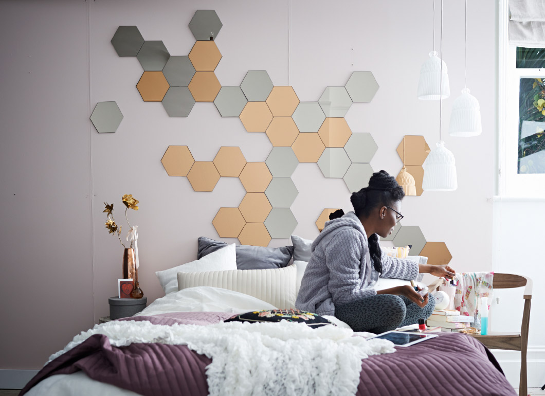 Young woman sitting on her cosy IKEA double bed