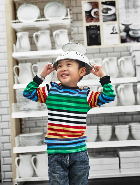 Young boy at an IKEA store with a GEMAK colander on his head.