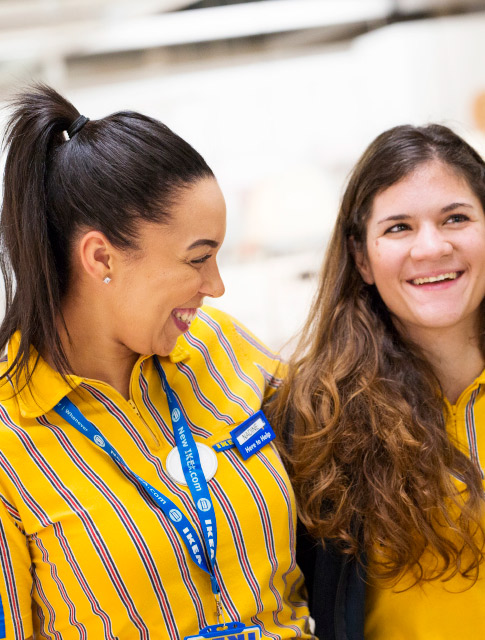 Close up of two IKEA store co-workers looking very happy.