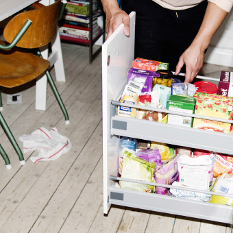 Father opening pantry drawer in kitchen. In Stockholm home.