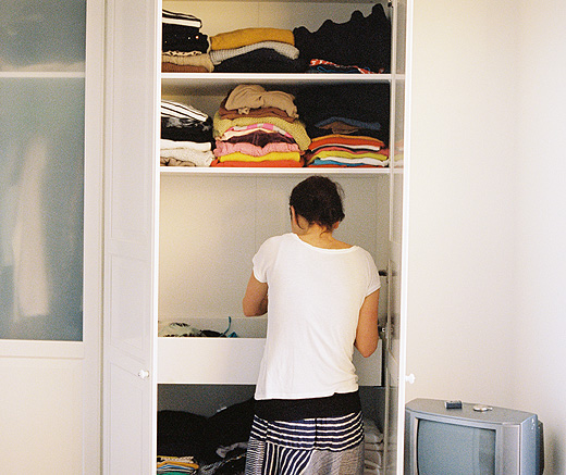 A person organizing clothes in a wardrobe.