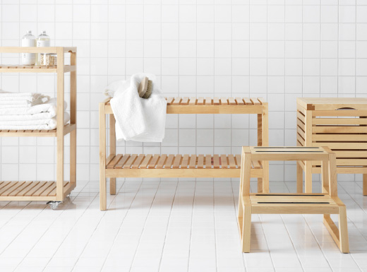 A fully white tiled room with a birch shelf, a birch bench, a birch stool and one birch floor cube storage unit