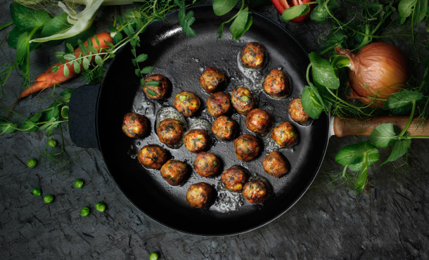 IKEA veggie balls in a cast iron pan surrounded by an onion, a carrot and greenery.