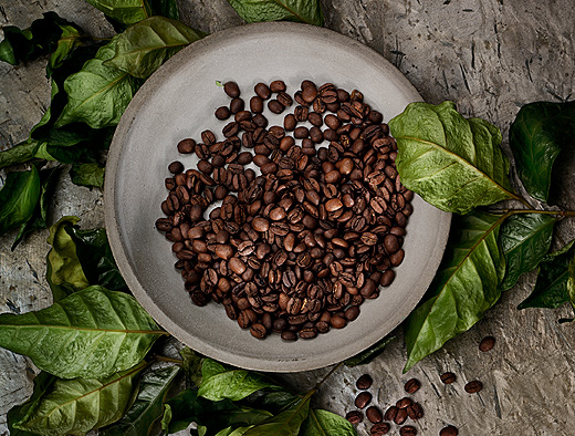 Coffee beans on a grey plate shown together with green leaves, seen from above.