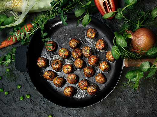 Fried vegetable balls in a frying pan made of cast iron, seen from above.