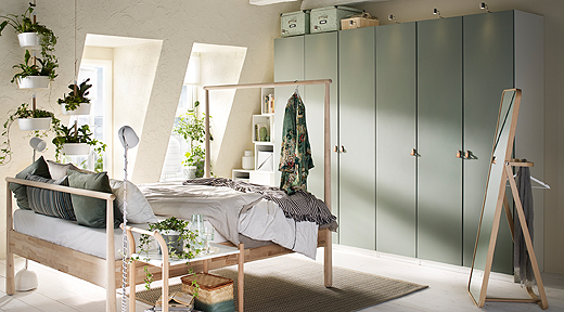 An image showing the REINSVOLL wardrobe doors, made of recycled wood and plastic foil from recycled PET bottles, in a bedroom setting.