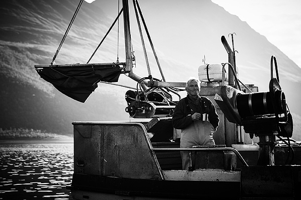 A black and white photo of a man standing on a fishing boat with a mountain in the background.