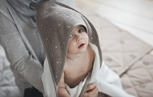 A baby wrapped in a white/beige baby towel with a hood, sitting in her mother's knee.