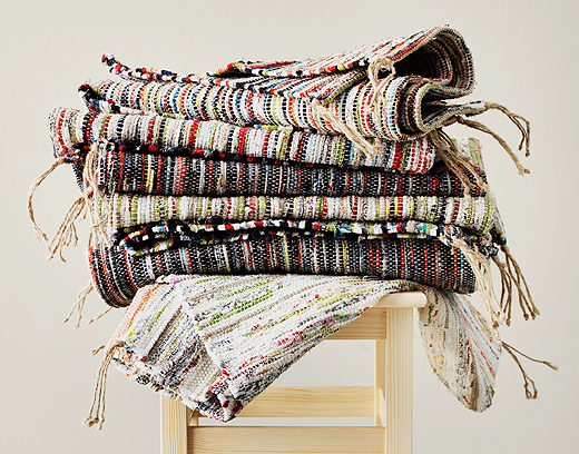 A stool with a pile of rag-rugs made with leftover fabric from bedlinen.